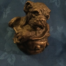Heavy bronze puppy in a knap sack