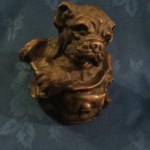 Heavy bronze puppy in a knap sack